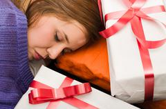 Brunette covered with purple clothing sleeping, resting head between presents Stock Photos