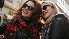 Two adorable young friends in sunglasses taking selfies on the street - stock footage
