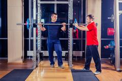 Sport, fitness, teamwork, bodybuilding people concept - man and personal trainer Stock Photos