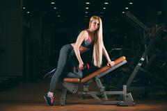 Brutal athletic woman pumping up muscles with dumbbells in gym - stock photo