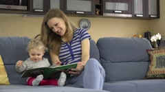 Nanny woman story telling read book for child at kindergarten at work - stock footage