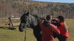 The horse riding trainer helps the female beginner to mount for the first time Stock Footage