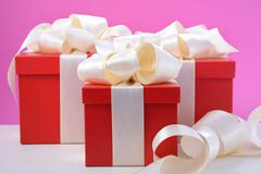 Red and white gifts on pink background. - stock photo