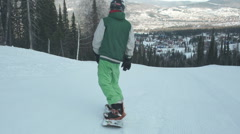 Snowboarder coming down on an empty snow-covered road - stock footage