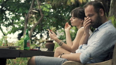 Offended, bored couple sitting in outdoor cafe in garden Stock Footage
