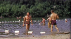 1952: Adult men flirting play splashy in public swimming lake park. Stock Footage