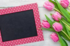 Pink Tulips on a white background with a blackboard - stock photo