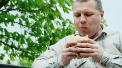 Brutal middle-aged man to eat fast food outdoors Stock Footage