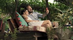 Happy couple taking selfie photo with cellphone in outdoor cafe in garden Stock Footage