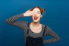 Cheerful cute young woman covered one eye by hand - stock photo