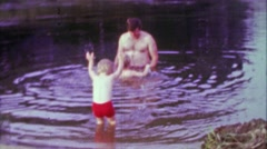 1967: Fun hairy soft dad playing with kids in dirty pond water. Stock Footage
