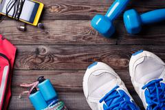 Sports equipment - sneakers, skipping rope, dumbbells, smartphone and headphones - stock photo