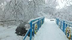 Walking over small bridge over winter river in Novosibirsk Akademgorodok Stock Footage