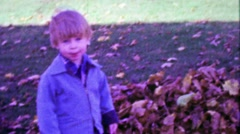1967: Blue eyed kid with bowl haircut playing in autumn fallen leaves. Stock Footage