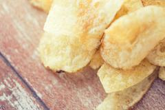 close up of crunchy potato crisps on wooden table - stock photo