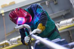 Industrial worker welding in metal factory. - stock photo
