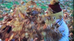 1967: Kid brothers playing in autumn leaf pile toss baby unsure. - stock footage