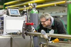 Industrial worker setting orbital welding machine. Stock Photos
