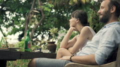 Happy couple relaxing in outdoor cafe in garden Stock Footage