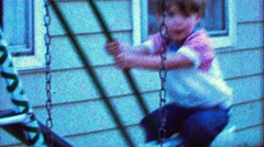 1967: Confident boy swings high on swings too close to house. - stock footage