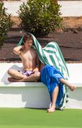 Cute boys sitting on a bench at the pool Stock Photos