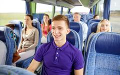 Happy young man sitting in travel bus or train Stock Photos