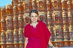 beautiful european woman in front of Hawa Mahal in Jaipur, Rajasthan, India. - stock photo