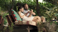 Couple talking and using smartphone sitting in outdoor cafe in garden Stock Footage