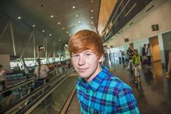 young boy on a moving staircase inside the airport - stock photo
