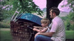1967: Father lets son drive riding lawn mower across rural country yard. Stock Footage