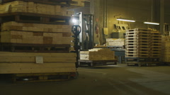 Forklift operator is driving in lumber factory warehouse Stock Footage