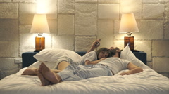 Couple in bed at night, man texting with lover on smartphone, wife sleeping Stock Footage
