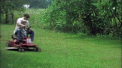 1967: Father son riding lawn mower together teaching how to drive. Stock Footage