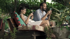 Young couple with tablet and smartphone sitting in outdoor cafe in garden Stock Footage