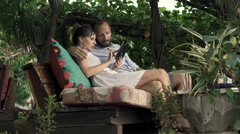 Couple talking and using tablet sitting in outdoor cafe in garden Stock Footage