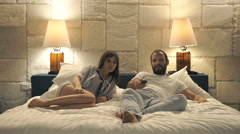 Young couple watching TV on bed at night at home Stock Footage