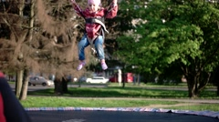 Little Girl Bouncing on a Bungee Trampoline Stock Footage