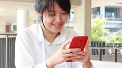 Portrait of thai student university beautiful girl using her smart phone. Stock Footage