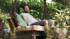 Young man relaxing in outdoor cafe in garden Stock Footage