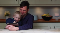 Father and son use an electronic tablet at the kitchen table Stock Footage