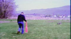 1968: Dad swings wiffle baseball bat hits ball showing kids how it's done. Stock Footage