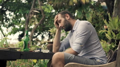 Sad, unhappy man waiting for someone in outdoor cafe in garden Stock Footage
