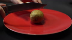 Knife Cut Kiwi Fruit on a Red Round Dish Stock Footage