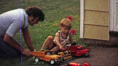 1968: Dad and son playing toy model dump and fire trucks backyard. Stock Footage