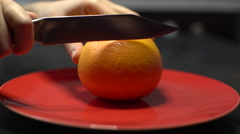 Knife Cut Orange on a Plate on a Red Round Dish Stock Footage
