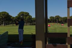 Golf player practicing shot on training Stock Photos