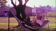 1968: Dad relaxing in hammock enjoying shade in hot summer days. Stock Footage