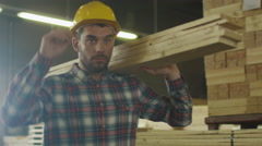 Lumber mill worker in hardhat is carrying wood in warehouse - stock footage