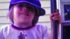 1968: Boy wearing dad's hippie cap style hat with cartoon bear shirt. Stock Footage