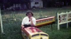 1952: Duty bound mother complacently taking kids on mini play train ride. Stock Footage